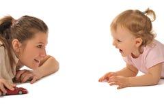 La ragazza con il piccolo bambino in studio sta giocando Fotografia Stock Libera da Diritti