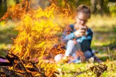 La ragazza con il telefono è discreto visibile da fuoco e da fumo dal falò in autunno nel woods_ immagini stock libere da diritti