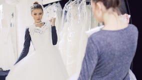 La ragazza con il vestito da sposa esibe la parte anteriore dello specchio stock footage