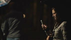 La ragazza con l'ombrello utilizza il suo telefono cellulare alla notte sui precedenti della città stock footage