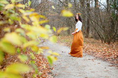 La ragazza con la corona del fiore va sentiero per pedoni nel parco di autunno Fotografie Stock Libere da Diritti