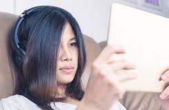 La ragazza con la cuffia sta guardando il contenuto sulla compressa fotografia stock