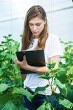 La ragazza con la lavagna per appunti prende le note riguardo alle piante Immagine Stock Libera da Diritti