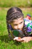 La ragazza con la lente d'ingrandimento e lo scarabeo mette sull'erba Fotografia Stock