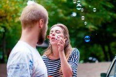 La ragazza con le bolle di sapone lo soffia verso il tipo Bolle felici di sapone e della ragazza Fotografia Stock Libera da Diritti