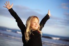 La ragazza con le braccia outstretched sulla spiaggia Fotografie Stock Libere da Diritti
