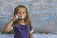 La ragazza con le ferite sul suo fronte soffia le bolle di sapone Immagine Stock