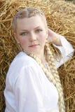 La ragazza con le intrecciature in una camicia bianca Immagine Stock