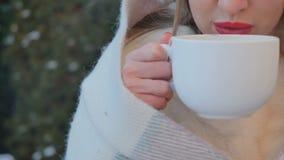 La ragazza con le labbra rosse beve un tè caldo per riscaldare all'inverno all'aperto stock footage