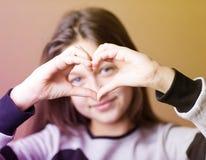 La ragazza con le mani ha dipinto il cuore Fotografia Stock