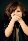 La ragazza con lei cosegna la sua bocca Fotografia Stock