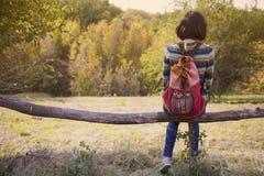 La ragazza con lo zaino che riposa nella foresta Fotografie Stock Libere da Diritti