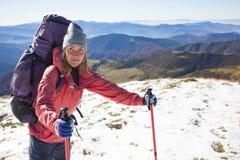 La ragazza con lo zaino passa attraverso la neve Fotografia Stock