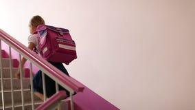 La ragazza con lo zaino rosa va di sopra alla stanza di classe a scuola La ragazza con lo zaino va a casa dopo lo studio in eleme stock footage