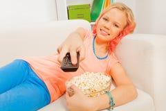 La ragazza con popcorn sul sofà tiene il telecomando Fotografie Stock