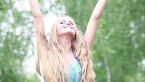 La ragazza con un bello sorriso sviluppa i capelli lunghi sulla natura video d archivio