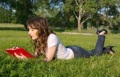 La ragazza con un blocco note e la penna di estate parcheggiano sull'erba Fotografie Stock