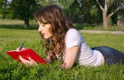 La ragazza con un blocco note e la penna di estate parcheggiano sull'erba Immagini Stock
