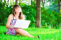 La ragazza con un computer portatile Fotografie Stock