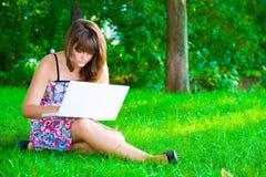 La ragazza con un computer portatile Immagine Stock