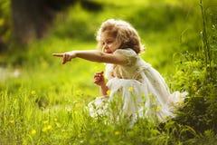 La ragazza con un fiore indica da qualche parte la mano Immagine Stock