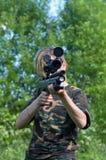 La ragazza con un fucile ad aria compressa. Immagini Stock