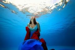 La ragazza con un panno rosso e blu in sue mani galleggia underwater alla superficie del mare dal fondo Fotografia Stock