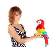 La ragazza con un pappagallo del giocattolo Fotografia Stock