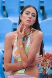 La ragazza con un tatuaggio dell'istantaneo dell'oro sul suo braccio tocca il suo collo fotografia stock libera da diritti