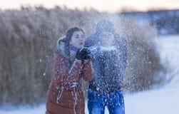 La ragazza con un tipo soffia via la neve Fotografia Stock Libera da Diritti