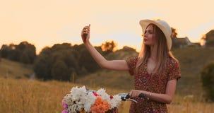 La ragazza con una bici in un cappello fa un selfie facendo uso di uno smartphone archivi video
