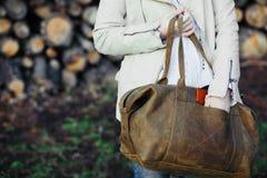 La ragazza con una borsa di cuoio ad una parete dai ceppi fotografie stock libere da diritti