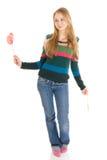 La ragazza con una caramella di zucchero isolata su un bianco Immagine Stock