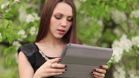 La ragazza con una compressa digitale nel giardino video d archivio