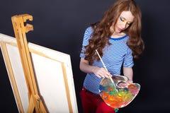 La ragazza con una gamma di colori e una spazzola vernicia un pictu Immagini Stock Libere da Diritti