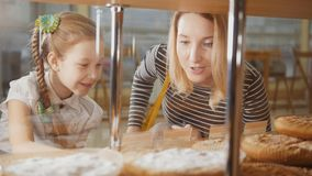 La ragazza con una treccia e la sua mamma esaminano le torte nella finestra che sceglie fotografia stock libera da diritti