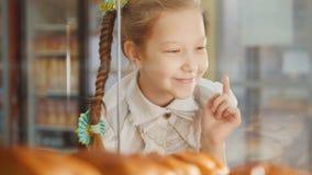 La ragazza con una treccia esamina le torte nella finestra che sceglie fotografie stock libere da diritti