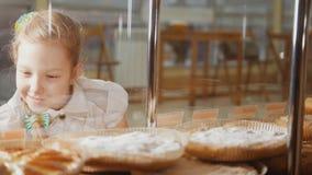 La ragazza con una treccia esamina le torte nella finestra che sceglie immagine stock