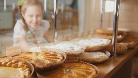 La ragazza con una treccia esamina le torte nella scelta della finestra, de-messa a fuoco fotografia stock libera da diritti