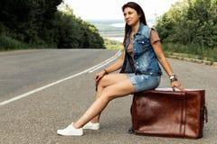 La ragazza con una valigia ferma l'automobile sulla strada fotografie stock libere da diritti