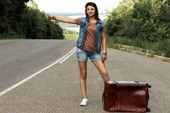 La ragazza con una valigia ferma l'automobile sulla strada fotografia stock libera da diritti