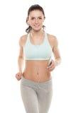 La ragazza con uno smartphone su un fondo bianco, gode degli sport preparantesi, allenamento di forma fisica della palestra Immagine Stock