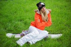 La ragazza con uno snowboard sta sedendosi sull'erba immagine stock