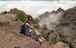 La ragazza con uno zaino si siede ha un resto su una pista pietrosa altamente Fotografia Stock
