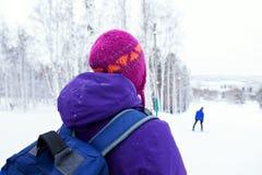 La ragazza con uno zaino su un fianco di una montagna nevoso Fotografie Stock Libere da Diritti