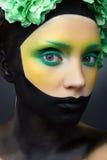 La ragazza con verde e nero creativi compone e fiori Fotografia Stock