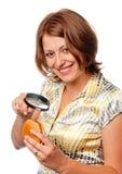 La ragazza considera un hamburger tramite un magnifier Fotografia Stock Libera da Diritti