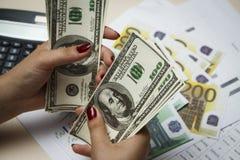 La ragazza conta molte cento banconote in dollari Fotografia Stock