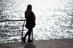 La ragazza contempla l'abbagliamento di luce solare nel mare Immagini Stock