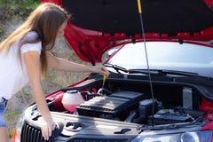 La ragazza controlla il livello di olio nell'automobile fotografia stock libera da diritti